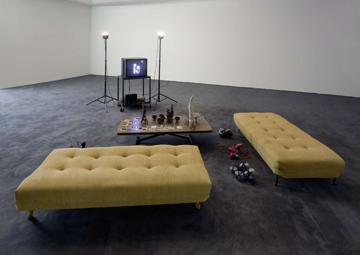 Manuel Graf, Buchtipp 2, two sofa, table, TV monitor, lamps, ceramic ( 10 parts ), five shoes, 20 polaroid, 2010, dimensions variable, unique