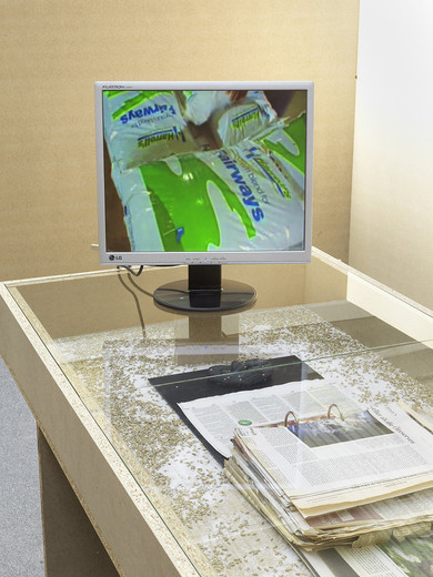 Tue Greenfort, Untitled, vitrine, newspaper articles, rye grains, urea crystals, bag with urea powder, 2 canisters, video, 2014, dimensions variable, unique