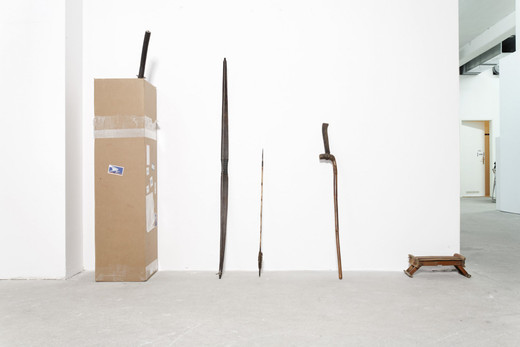 Danh Vo, untitled (coin), sword, bow, 4 parts, cardboard box, 14 document, framed, 2007, Sword 100 x 10 x 5 cm, Documents each 21 x 29,7 cm, Arrow 100 x 2 x 2 cm, Longbow 168 x 20 x 4 cm, Axe 120 x 10 x 4 cm, Cardboard                   145 x 30 x 30 cm, Bamboo headrest 10 x 30 x 20 cm., unique