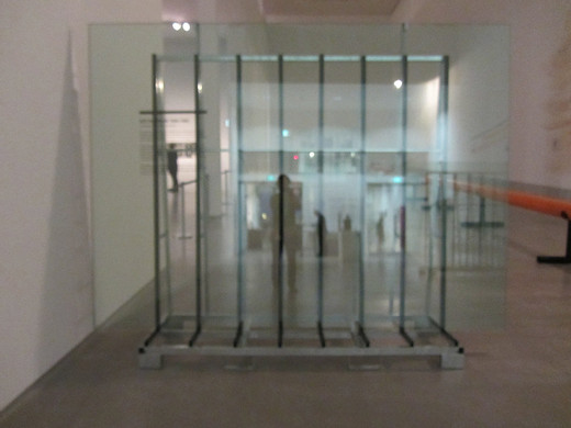 "Tue Greenfort, ERDGLAS – AVANTGARDE, glass transport rack, three float glass panes, wall text from the exhibition ""Art in Berlin 1880 - 1980"""""", 2012, 236 x 320 x 70.5 cm, unique"