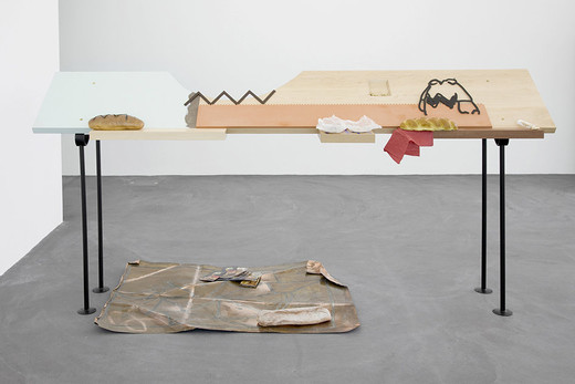 Helen Marten, Peanuts, Solid Ash; greasy orange Valchromat; sanded Formica; Cherry; Sepili; Walnut; resin/foam/latex breads and doughnuts; sesame seeds; sawdust; napkin; powder coated steel; pizza flyer from Betty Richter painting; soldered copper sheet; peanuts; steel cut from Charlie Brown profiles, 2012, rail legs each 120 x 55 cm top dimensions: 280 x 50 x 4.5 cm