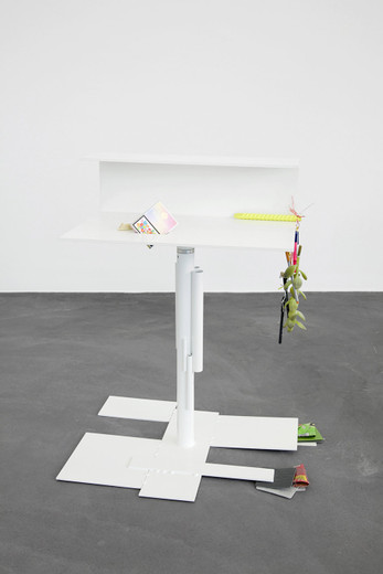 "<span class=""artists work-caption"">Helen Marten</span><span class=""title work-caption"">A face the same colour as your desk (6)</span><span class=""technique work-caption"">Welded/radial bent powder coated steel; stitched fabric; chocolate; cigarettes; cactuses; fruit; grinded rebar; plastic string; wood; pens; cardboard</span><span class=""year work-caption"">2012</span><span class=""dimensions work-caption"">90 x 60 x 70 cm</span><span class=""edition work-caption"">unique</span>"
