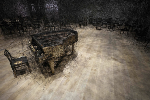 Chiharu Shiota, In Silence, 2019, Installation: burnt piano, burnt chairs, Alcantara black thread Mori Art Museum, Tokyo, Japan photos by Sunhi Mang, photo courtesy: Mori Art Museum, Tokyo © VG Bild-Kunst, Bonn, 2020 and the artist